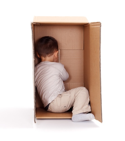 are hidden: Little boy hiding in cardboard box, playing peek-a-boo