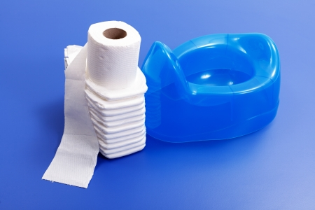 potty: White toilet paper and  stack of diapers beside blue potty on blue background