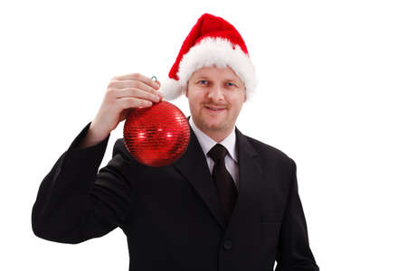 Businessman in Santa hat, showing red Christmas ornament photo