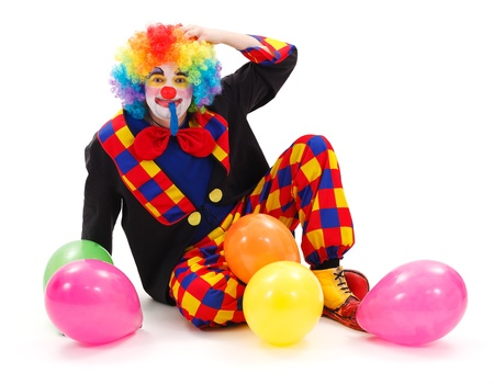 comedic: Clown sitting on floor, scraping his head, surrounded with colorful balloons
