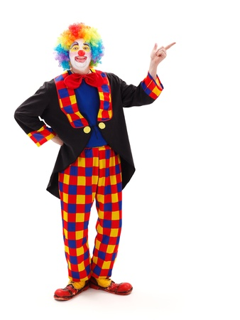 Funny clown pointing and calling attention for something on copy space