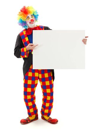 Smiling clown holding and pointing at blank white board photo