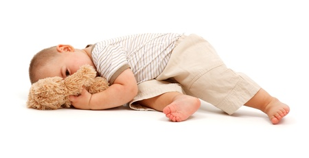 Tired little boy peeking from behind toy bear photo