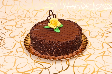 marzipan: Chocolate cake on golden plate with orange marzipan rose