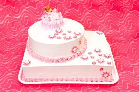 White christening cake for girl with pink decoration photo