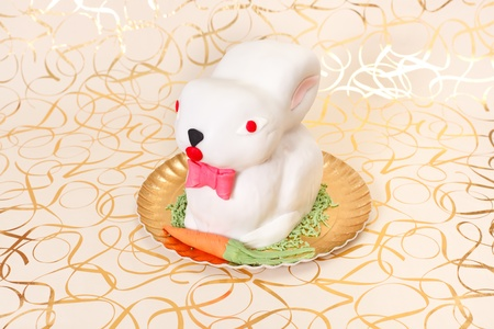 marzipan: White rabbit cake with marzipan carrot on golden plate and background