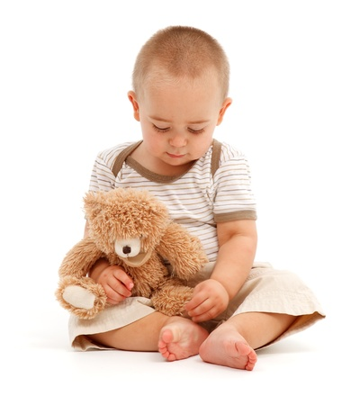 Sad little boy sitting and playing with his toy bear photo