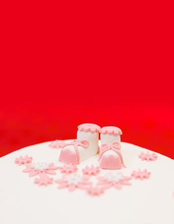 Closeup view of pink topper and flower decoration on baptist cake. Copy space above photo