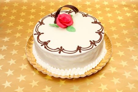 tortas cumpleaÑos: Pastel blanco con adornos de chocolate y mazapán rosa roja sobre fondo estrellas de oro