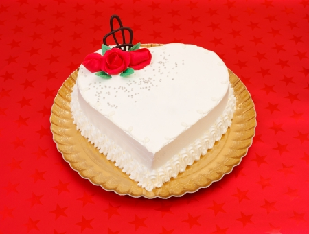 White heart cake with red marzipan roses on red background photo