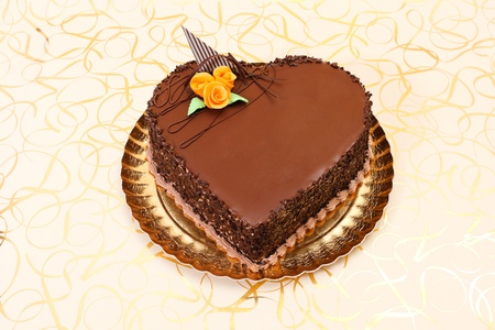 Chocolate heart cake on golden background photo