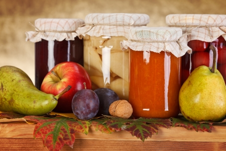 Close view of compotes and jam in glass bottle with fresh fruits