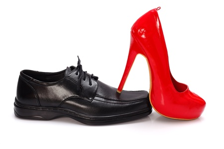 High-heeled red woman shoe on black man shoe - dominance concept Stock Photo - 17749486