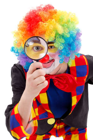 Smiling clown holding a big magnifying glass and looking through photo