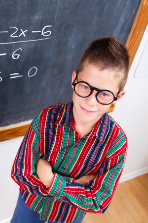 eminent: Eminent schoolboy wearing glasses, standing in front of chalkboard Stock Photo