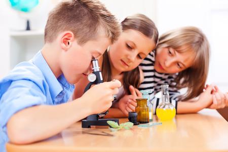 Leerlingen in de biologieles, die installatie door microscoop Stockfoto
