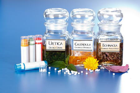 urtica: Various plant extract in bottles, Urtica Urens, Calendula Officinalis, Echinacea Angustifolia and homeopathic medication pills in front