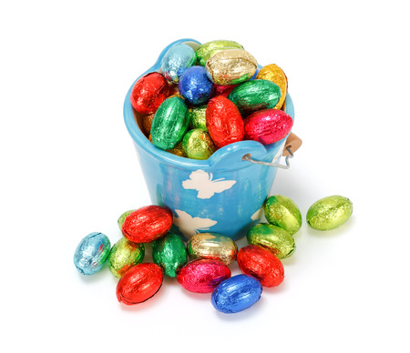 Colorful chocolate eggs in blue ceramic pail photo