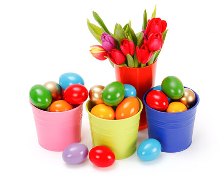Easter eggs in colorful tin buckets with a bouquet of tulips photo