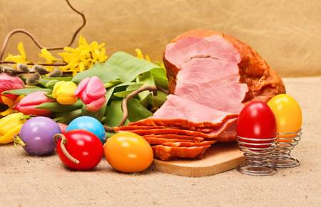 Boiled ham, painted Easter eggs and tulips on rustic table