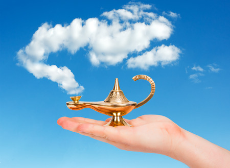 magic lamp: Aladdin lamp in human hand against cloudy sky Stock Photo