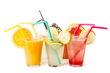Cool fresh juices in glasses, fruit slices and straw photo
