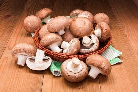 champignons: Fresh brown cultivated champignons in wooden board