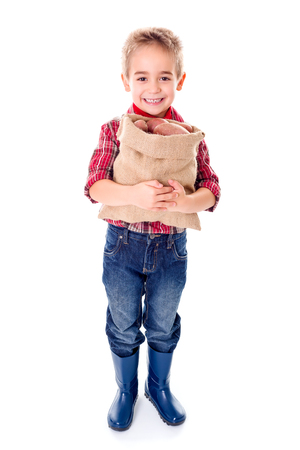 agriculturist: Happy little agriculturist boy holding a sack of red potatoes Stock Photo
