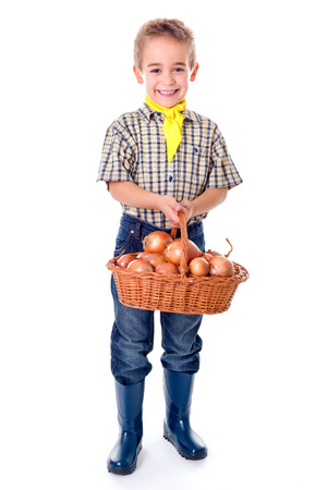 agriculturist: Little agriculturist boy holding big basket full with onions Stock Photo