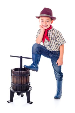 Casual little farmer boy posing with manual grape pressing tool photo