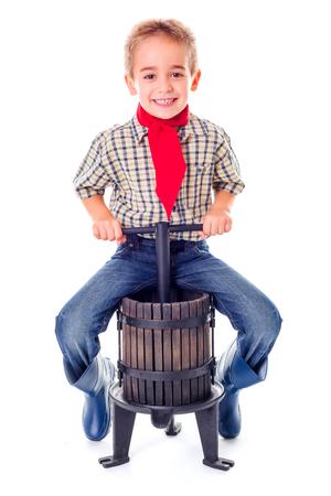 Casual little farmer boy sitting on manual grape pressing tool photo