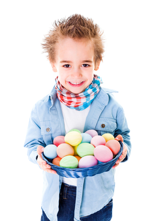 Close view of smiling boy showing an basket with colorful Easter eggs photo