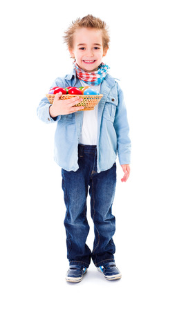 Cute little boy holding a basket with colorful painted Easter eggs photo