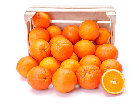 sinensis: Ripe oranges spilling out of wooden crate. Citrus sinensis Stock Photo