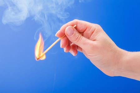matchstick: Hand holding a burning matchstick on blue background