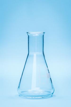 erlenmeyer: Chemical laboratory glassware, empty 100 milliliter Erlenmeyer flask on blue Stock Photo