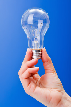 incandescent: Hand holding a clear incandescent light bulb on blue background