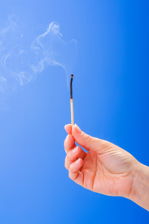 Hand holding burnt fuming matchstick on blue background photo
