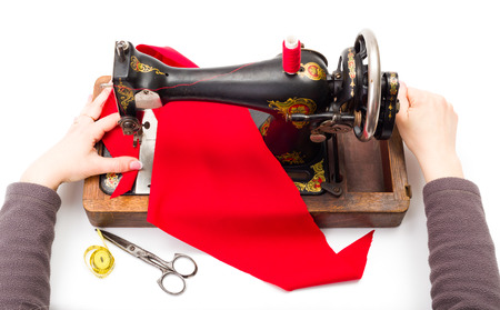 driven: Woman using an old hand driven sewing machine