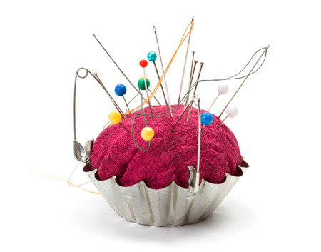 pinhead: Push pins, needles and safety pins clustered in pincushion Stock Photo