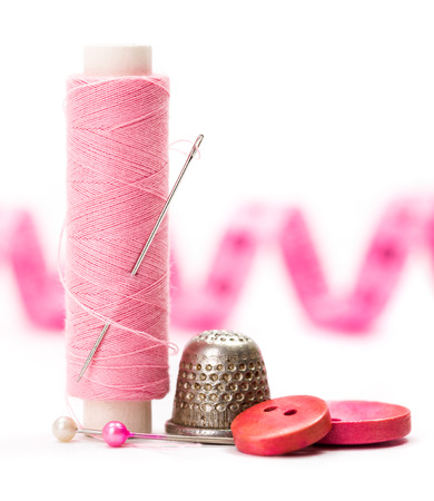 thimble: Pink sewing accessories: thread, needle, buttons, thimble and measuring tape Stock Photo