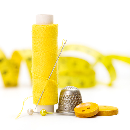 thimble: Yellow sewing accessories: thread, needle, buttons, thimble and measuring tape