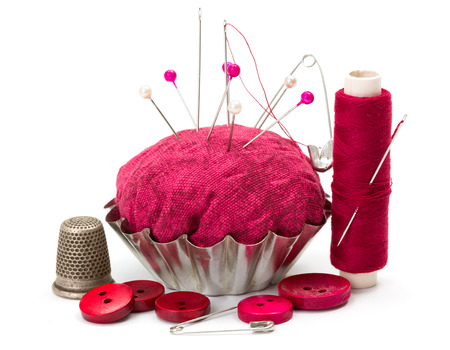 Pink sewing accessories: thread, needle, buttons, thimble and pincushion photo