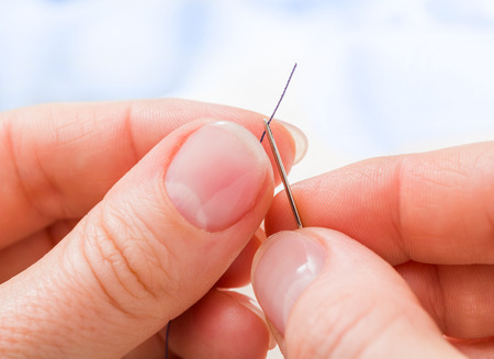 threading: Macro of womans hand threading a needle Stock Photo