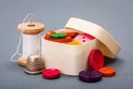 sewing box: Colorful buttons in wooden box near sewing thread and thimble