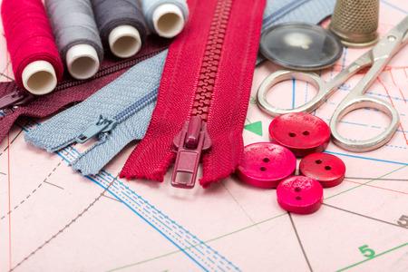 kit de costura: Accesorios rojos y grises de costura en el corte patrón