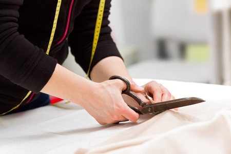 Dressmaker cutting fabric with big old steel scissors