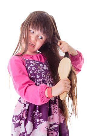 frizzy: Nervous little girl combing her frizzy hair