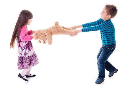 pull toy: Disputas niño y niña separando oso de juguete Foto de archivo