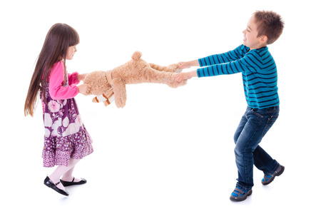 Wrangling boy and girl pulling apart toy bear Stockfoto